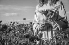有长的头发的一个年轻迷人的女孩在鸦片领域的一个明亮的晴朗的夏日走并且做花束鸦片花 免版税图库摄影