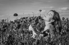 有长的头发的一个年轻迷人的女孩在鸦片领域的一个明亮的晴朗的夏日走并且做花束鸦片花 免版税库存照片