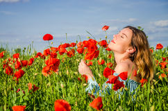 有长的头发的一个年轻迷人的女孩在鸦片领域的一个明亮的晴朗的夏日走并且做花束鸦片花 库存照片