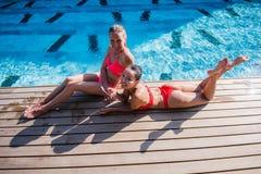 有长的头发的两个可爱的白肤金发和深色的女孩在弗洛尔说谎在水池附近 他们穿比基尼泳装和泳装 他们 免版税库存照片