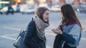 有长的头发的两个棕色毛发的时兴的可爱的学生女孩谈话,笑和拥抱在停车处的 影视素材