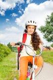 有长的头发的俏丽的女孩在盔甲骑自行车 库存照片