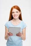 有长的头发的俏丽的微笑的红头发人夫人使用片剂 库存照片