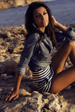 有长的黑发的华美的妇女穿牛仔裤衬衣,摆在沿海 免版税图库摄影