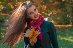 有长的头发的可爱的女孩在一条桃红色围巾在他的手保留它的叶子并且微笑 免版税图库摄影