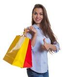 有长的黑发的可爱的妇女和显示拇指的购物袋 免版税库存照片