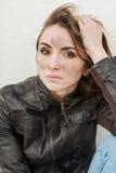 有长的头发的哀伤的女孩在皮夹克 免版税库存照片