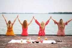 有长的头发的四个女朋友在甲板 免版税图库摄影