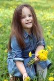 有长的头发的女孩在春天的会集蒲公英 免版税图库摄影