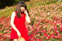 有长的头发的女孩在玫瑰园里 免版税库存图片