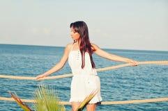 有长的头发的女孩在码头的一件短的白色礼服 免版税库存图片