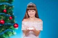 有长的头发的女孩在红色盖帽在一棵新年树附近花费 免版税库存图片