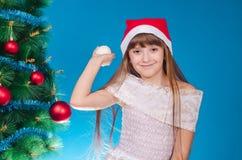 有长的头发的女孩在红色盖帽在一棵新年树附近花费 库存图片