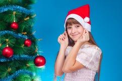 有长的头发的女孩在红色盖帽在一棵新年树附近花费 免版税库存照片