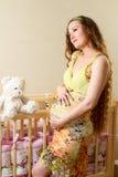 有长的头发的孕妇有玩具在小儿床的玩具熊的在家。 免版税库存照片