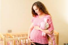 有长的头发的孕妇有玩具在小儿床的玩具熊的在家 库存图片