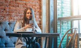 有长的头发的少妇坐在桌上靠近在咖啡馆和用途智能手机的窗口 免版税库存照片
