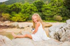 有长的头发的快乐的女孩在一件白色礼服坐岩石由海 图库摄影
