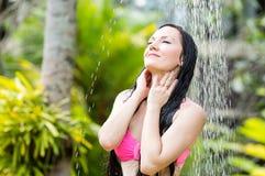 有长的头发的性感的妇女在阵雨下的比基尼泳装在热带海滩 库存照片