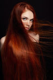 有长的头发的性感的美丽的红头发人女孩 在黑背景华美的头发和深眼睛的完善的妇女画象 自然的秀丽 库存图片
