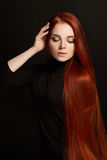 有长的头发的性感的美丽的红头发人女孩 在黑背景华美的头发和深眼睛的完善的妇女画象 自然的秀丽 图库摄影
