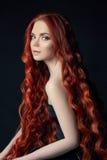 有长的头发的性感的美丽的红头发人女孩 在黑背景的完善的妇女画象 华美的头发和深眼睛自然秀丽 库存照片