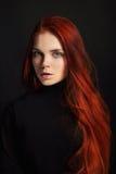 有长的头发的性感的美丽的红头发人女孩 在黑背景的完善的妇女画象 华美的头发和深眼睛自然秀丽 免版税库存照片