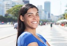 有长的黑发的愉快的拉丁妇女在城市 免版税库存图片