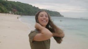 有长的头发的愉快的被晒黑的女孩走沿沙滩的 影视素材