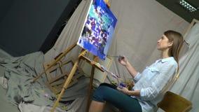 有长的头发的浅黑肤色的男人画在有油漆的一个画架站立坐椅子的图片,翻转照相机 股票视频