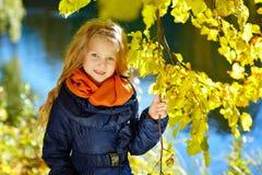 有长的头发的美丽的六岁的白肤金发的女孩微笑反对Th 免版税库存照片