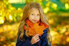有长的头发的美丽的六岁的白肤金发的女孩拿着一张地图 免版税库存照片