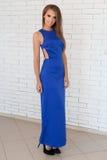 有长的头发的美丽的典雅的时髦时髦的女孩和在摆在为照相机的蓝色礼服的明亮的构成在演播室 免版税库存图片