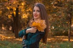 有长的头发的美丽的女孩在公园站立在转动斜向一边和拿着叶子花束旁边  免版税库存照片