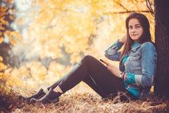 有长的黑发的美丽的女孩在秋天公园 库存图片