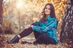 有长的黑发的美丽的女孩在秋天公园 库存照片