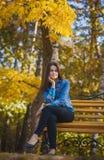 有长的黑发的美丽的女孩在秋天公园 免版税图库摄影