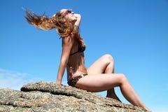 有长的头发的美丽的女孩在蓝天 免版税库存照片