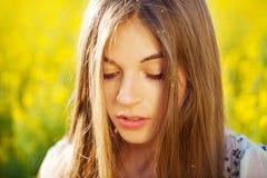 有长的头发的美丽的女孩在黄色花 库存图片
