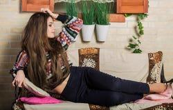 有长的黑发的美丽的女孩坐长凳在房子附近在窗口下 免版税库存图片