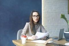 有长的头发的美丽的女实业家与文献,板料,膝上型计算机一起使用,当坐在现代顶楼办公室时 免版税库存照片