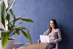 有长的头发的美丽的女实业家使用现代便携式计算机,当坐在他的现代顶楼办公室时 免版税图库摄影