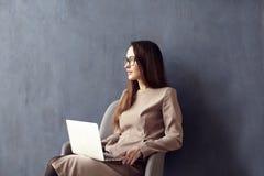 有长的头发的美丽的女实业家使用现代便携式计算机,当坐在他的现代顶楼办公室时 免版税库存图片