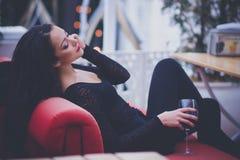 有长的头发的美丽的妇女喝红葡萄酒的在餐馆 免版税库存照片