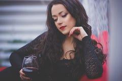 有长的头发的美丽的妇女喝红葡萄酒的在餐馆 免版税图库摄影