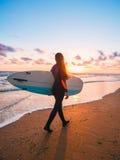有长的头发的美丽的妇女去冲浪 与冲浪板的Surfgirl在日落或日出的一个海滩 冲浪者和海洋 库存照片