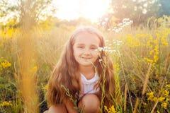 有长的头发的美丽的小女孩和微笑在日落的夏令时停放 库存图片