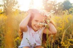 有长的头发的美丽的小女孩和微笑在日落的夏令时停放 免版税库存照片