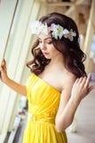 有长的头发的美丽的少妇在一个夏日 黄色礼服的女傧相在海餐馆 图库摄影