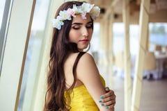 有长的头发的美丽的少妇在一个夏日 黄色礼服的女傧相在海餐馆 免版税图库摄影